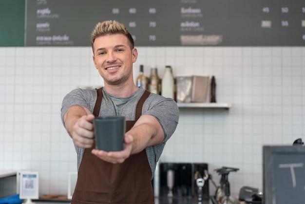 Homme propriétaire de barista de petite entreprise souriant et tenant une tasse de café à son client dans un café