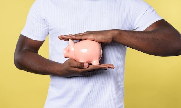 L'homme protège sa tirelire. concept d'épargne. fond jaune