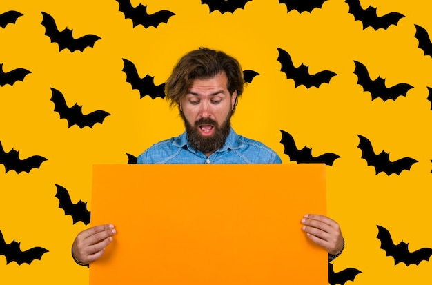 Homme de la publicité halloween avec panneau publicitaire joyeux halloween ventes et rabais sur les ventes d'automne
