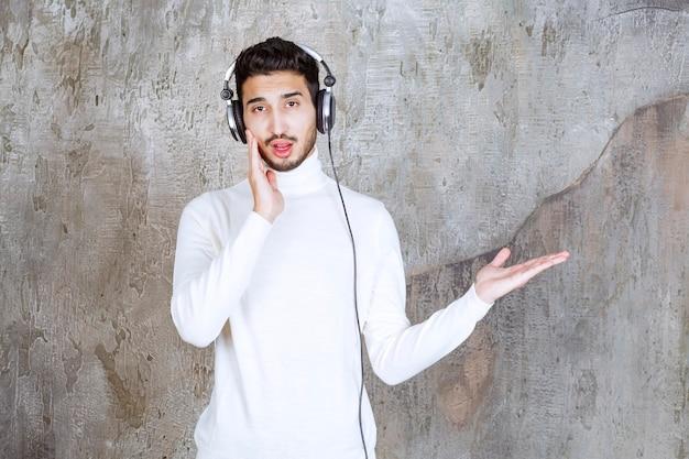 Homme en pull blanc portant des écouteurs et écoutant de la musique et montrant quelque chose autour.