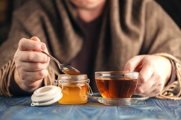 Homme en pull boire du thé chaud