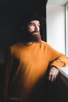Homme en pull à col roulé orange et chapeau fedora noir