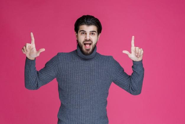Homme en pull gris pour pointer quelque chose ou présenter quelqu'un à l'aide du doigt pointé.