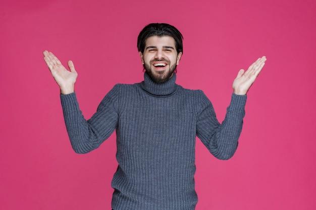 Homme en pull gris présentant ou saluant quelqu'un avec beaucoup d'énergie et d'enthousiasme.