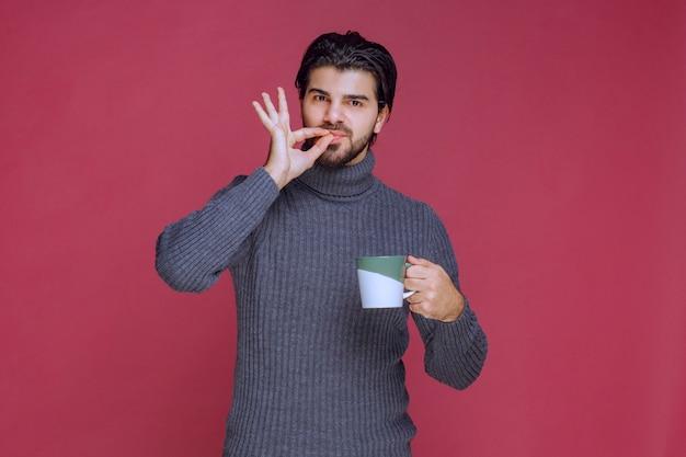 Homme en pull gris tenant une tasse de café et appréciant le goût.