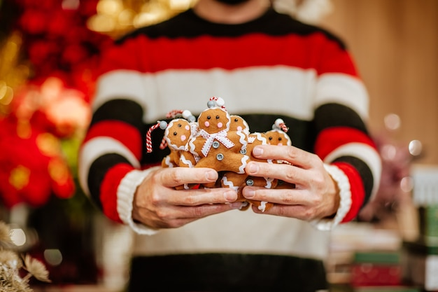 Homme en pull d'hiver noir et rouge et masque médical tenant des tas de biscuits jouets faits à la main