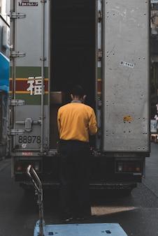 Homme en pull jaune derrière un camion gris