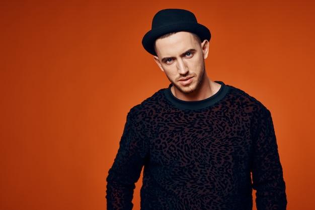 Homme en pull noir avec chapeau mode studio style moderne