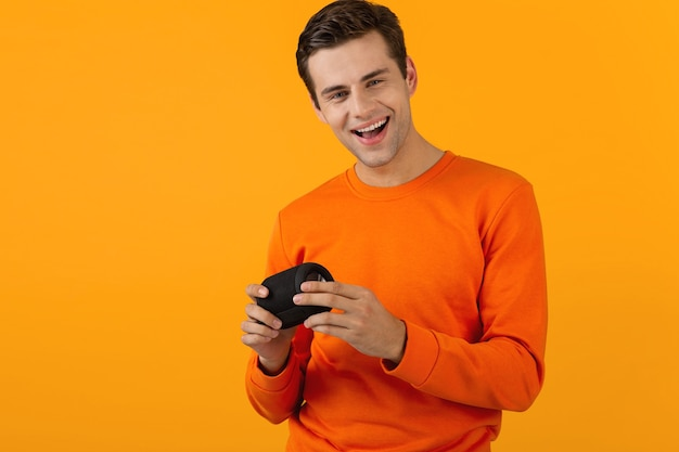 Homme en pull orange tenant un haut-parleur sans fil heureux d'écouter de la musique s'amusant isolé sur jaune