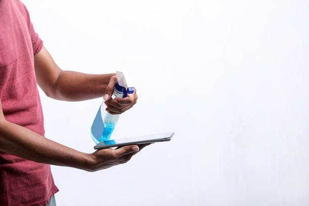 Homme pulvérisant de l'alcool, un spray désinfectant sur un téléphone portable, prévient l'infection du virus covid-19, la contamination de germes ou de bactéries, essuie ou nettoie le téléphone pour éliminer, épidémie de coronavirus