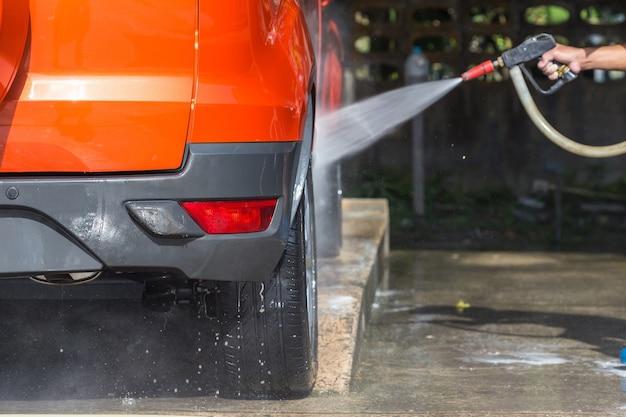 Un homme pulvérisant un nettoyeur haute pression pour un lavage de voiture dans un atelier de soins de la voiture