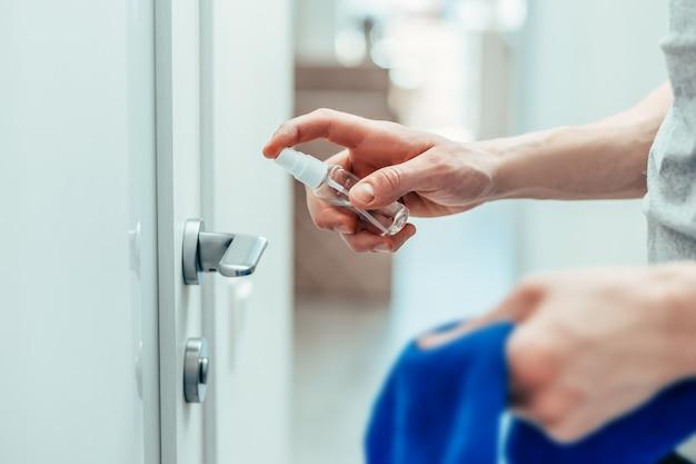 Homme pulvérisant un spray antiseptique sur la poignée de porte