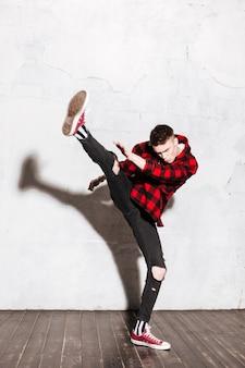 Homme punk en chemise faisant un coup de pied haut