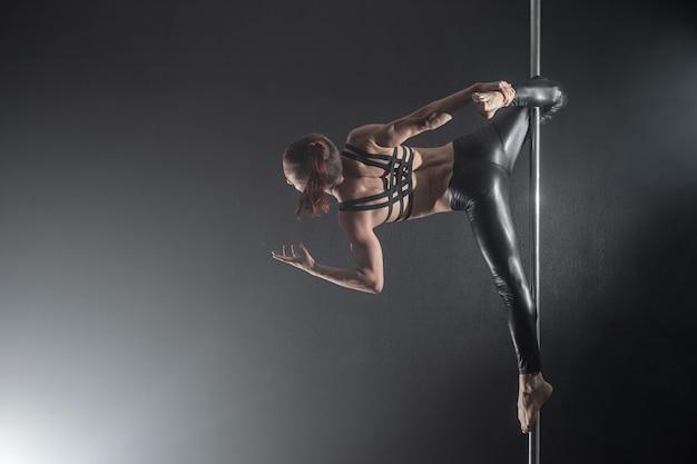 Homme avec pylône. danseur de pôle mâle danser sur un fond noir
