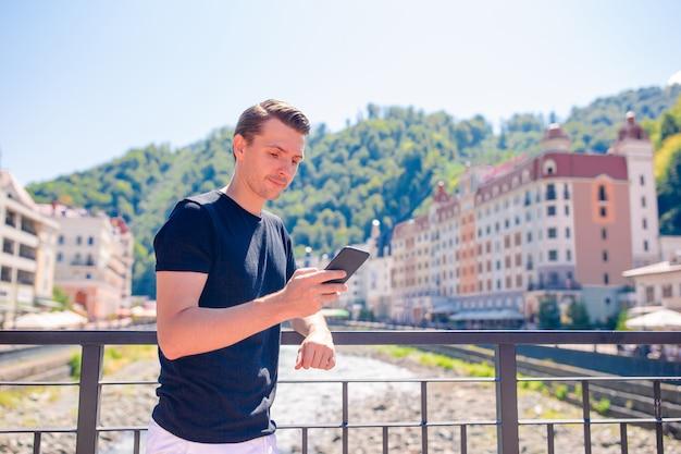 Homme sur le quai d'une rivière de montagne dans une ville européenne,