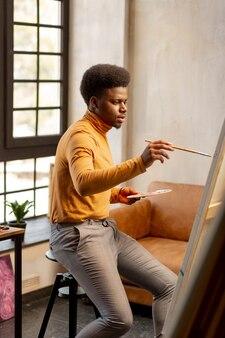 Homme qualifié sérieux tenant un pinceau tout en peignant une belle photo dans son studio