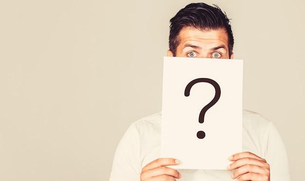 Homme une question. homme douteux tenant le point d'interrogation. problèmes et solutions. espace de copie