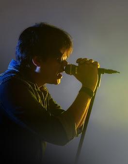 Un homme qui chante dans un micro sous le feu des projecteurs avec de la fumée sur une scène