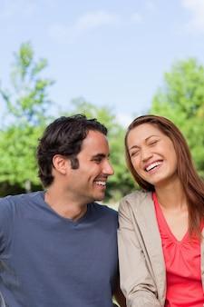 Homme qui cherche son amie alors qu'elle rit dans la joie assis dans un parc