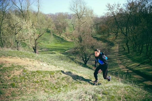 Homme qui court dans un parc ou une forêt contre les arbres