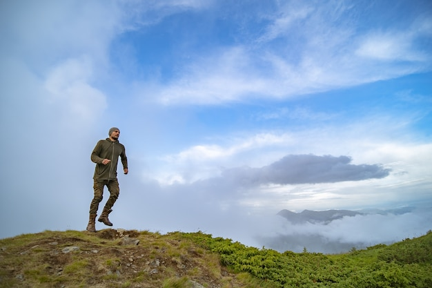 L'homme qui court sur la montagne sur le fond de ciel nuageux