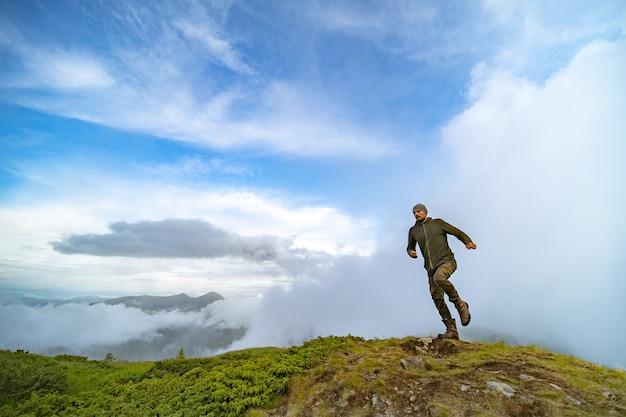 L'homme qui court sur la montagne sur un fond de ciel nuageux