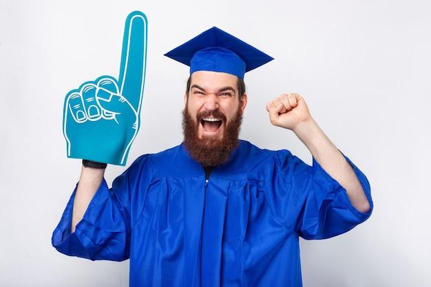 Un homme qui crie excité porte un gant d'éventail et fait le geste gagnant.