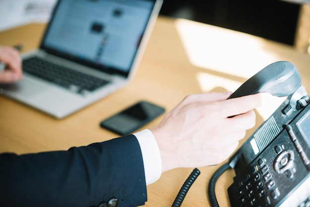 Homme qui décroche le téléphone au bureau