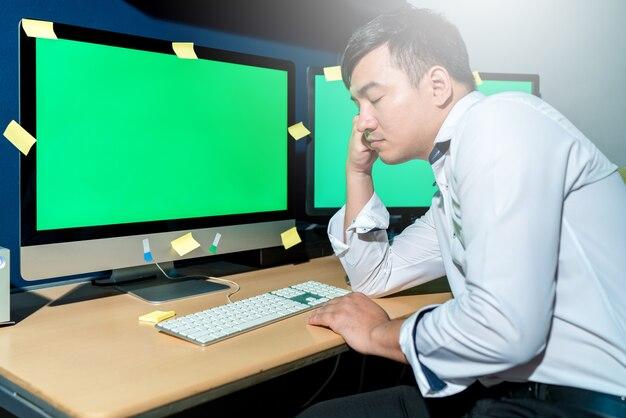 L'homme qui dort travaille sur une table au bureau
