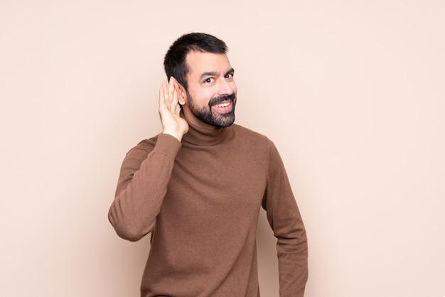 Homme qui écoute quelque chose en mettant la main sur l'oreille