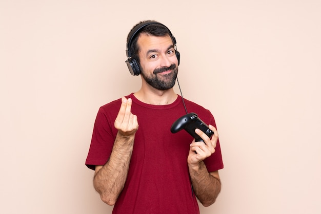 Homme qui joue avec un contrôleur de jeu vidéo, geste d'argent