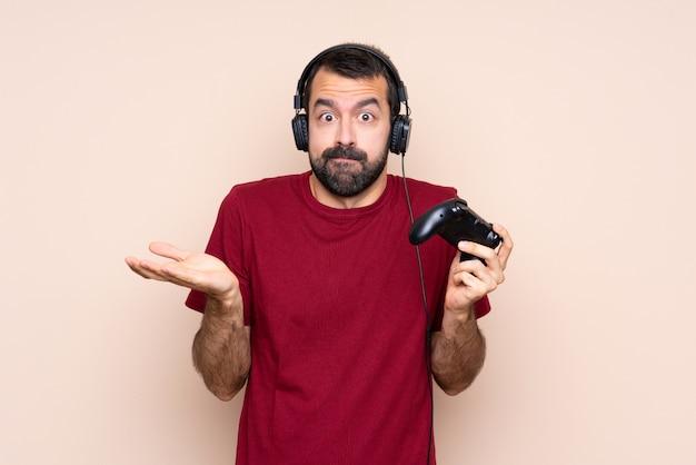 Homme qui joue avec un contrôleur de jeu vidéo sur un mur isolé ayant des doutes tout en levant les mains
