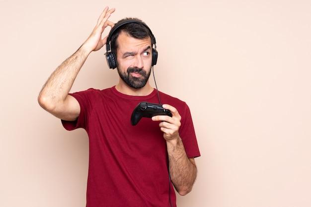 Homme qui joue avec un contrôleur de jeu vidéo sur un mur isolé ayant des doutes tout en se grattant la tête
