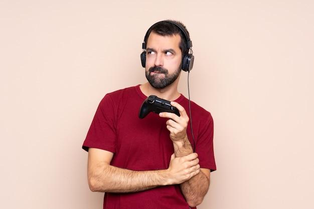 Homme qui joue avec un contrôleur de jeu vidéo sur un mur isolé avec une expression de visage confuse