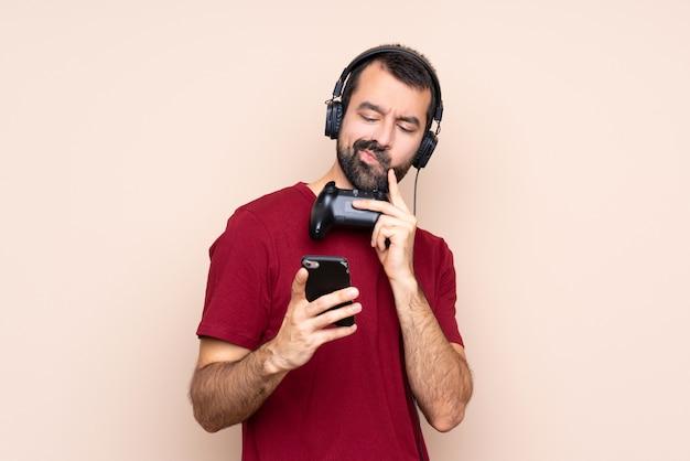 Homme qui joue avec un contrôleur de jeu vidéo sur un mur isolé, pensant et envoyant un message