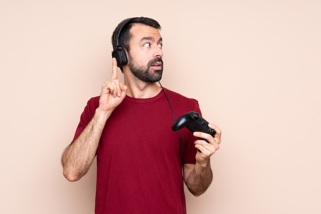 Homme qui joue avec un contrôleur de jeu vidéo sur un mur isolé, pensant une idée pointant le doigt vers le haut