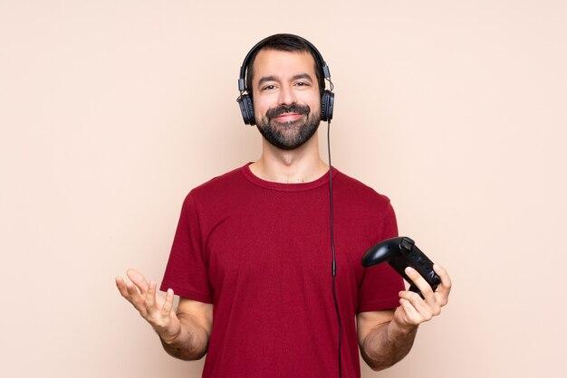Homme qui joue avec un contrôleur de jeu vidéo sur un mur isolé souriant