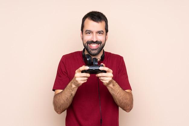 Homme qui joue avec un contrôleur de jeu vidéo sur un mur isolé