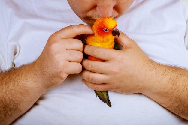 Homme qui joue avec son perroquet tenant coloré
