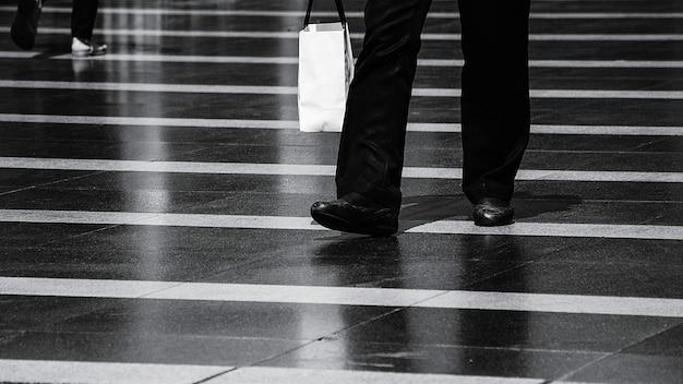 Homme qui marche dans la rue après le shopping en milieu urbain - monochrome