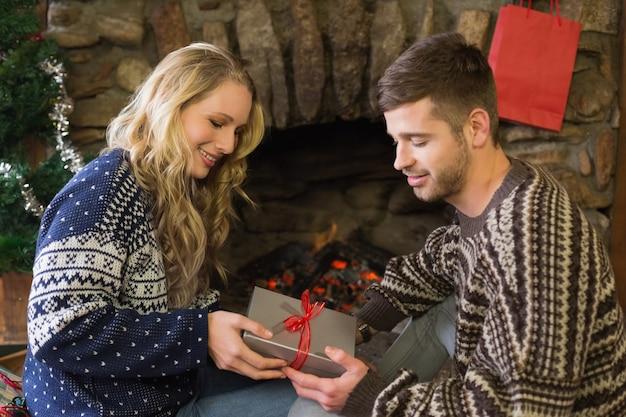 Homme qui offre une femme devant une cheminée allumée pendant noël