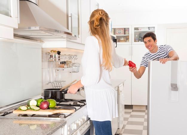 Homme qui passe des légumes à sa femme prépare des plats dans la cuisine