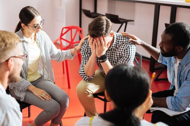 Homme qui pleure. homme nerveux émotionnel pleurant et fermant les yeux tandis que deux personnes fiables mettent gentiment les mains sur ses épaules
