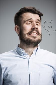 L'homme qui pleure avec des larmes sur le visage en gros plan sur le mur bleu