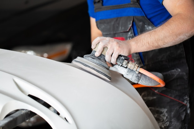 Un homme qui ponce avec un broyeur et prépare la peinture pour la voiture dans un service de voiture. réparer la peinture de voiture fixe