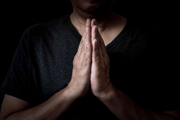 Un homme qui prie les mains respecte les choses sacrées.il a foi en dieu.sur fond noir