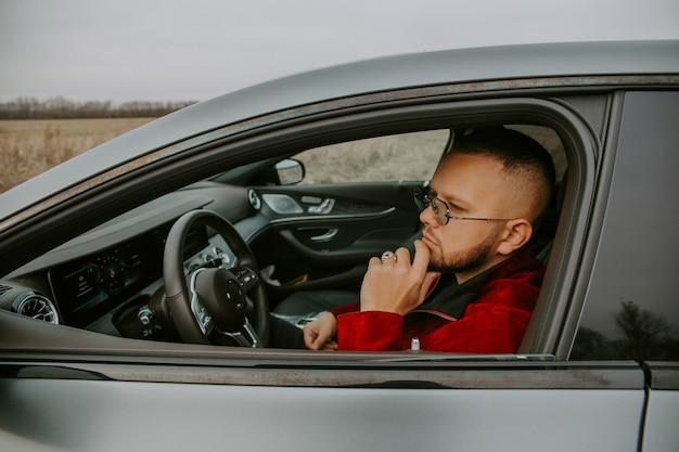 Homme qui a réussi au volant d'une voiture et portant des lunettes noires et une bague en or