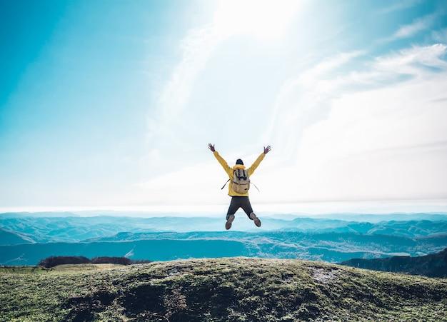 Homme qui réussit sautant au sommet de la montagne