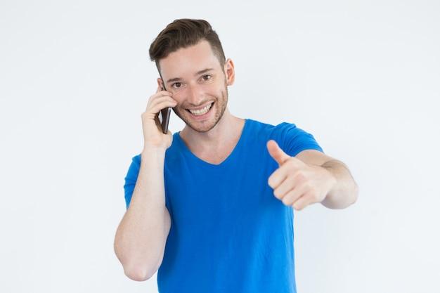 Un homme qui réussit en utilisant le téléphone et qui montre le pouce vers le haut
