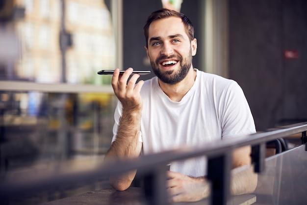 Homme qui rit avec smartphone et café